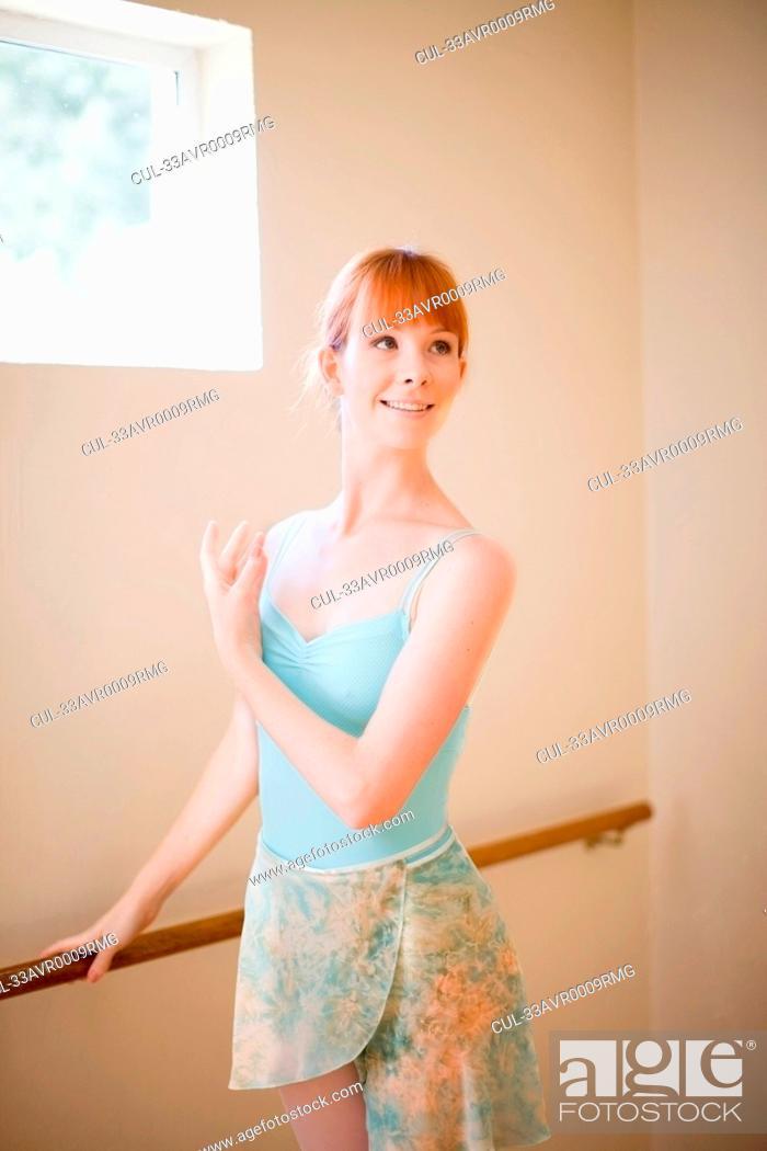 Stock Photo: Ballet dancer standing at barre.