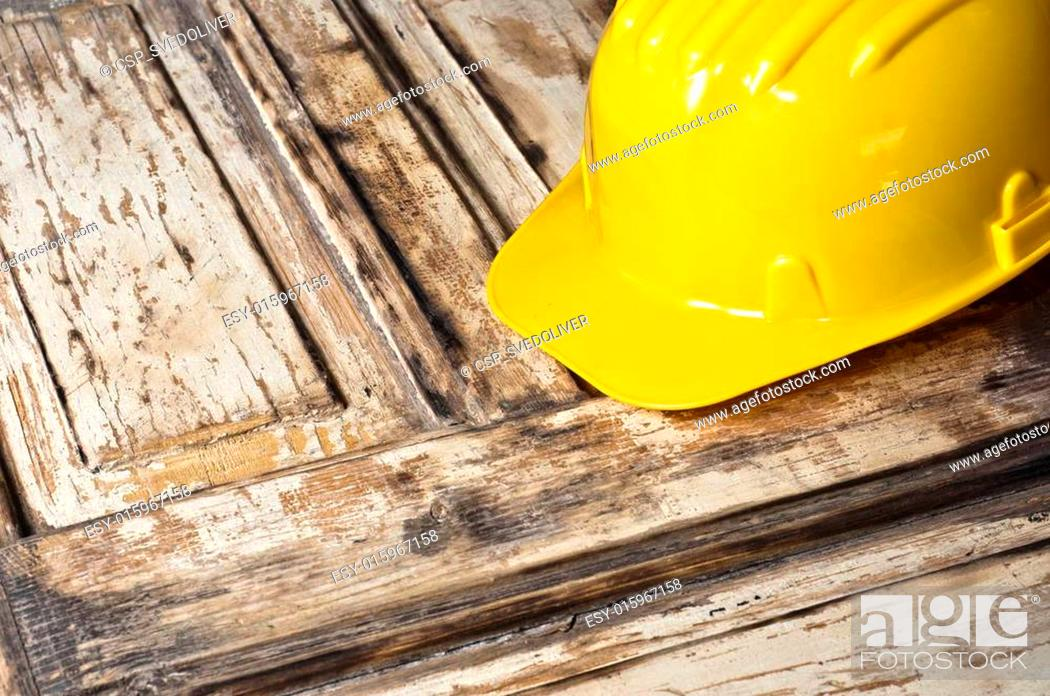 Stock Photo: Yellow helmet on burnt wooden log.