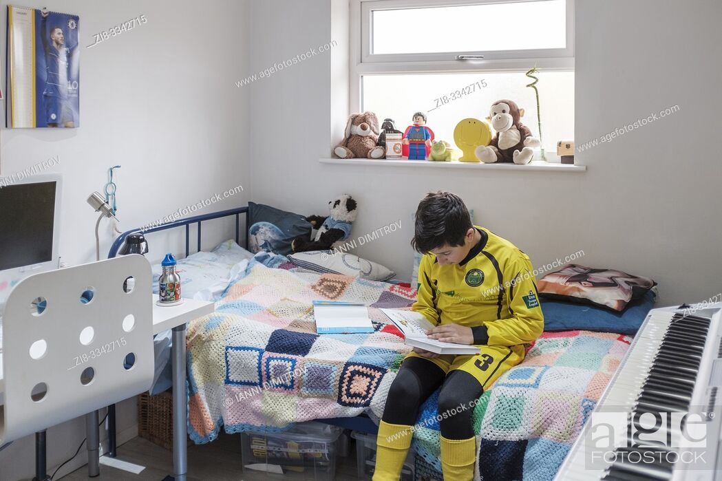 Stock Photo: England, Uk-Young boy, 11 years in Little league football outfit reads a book in his bedroom.