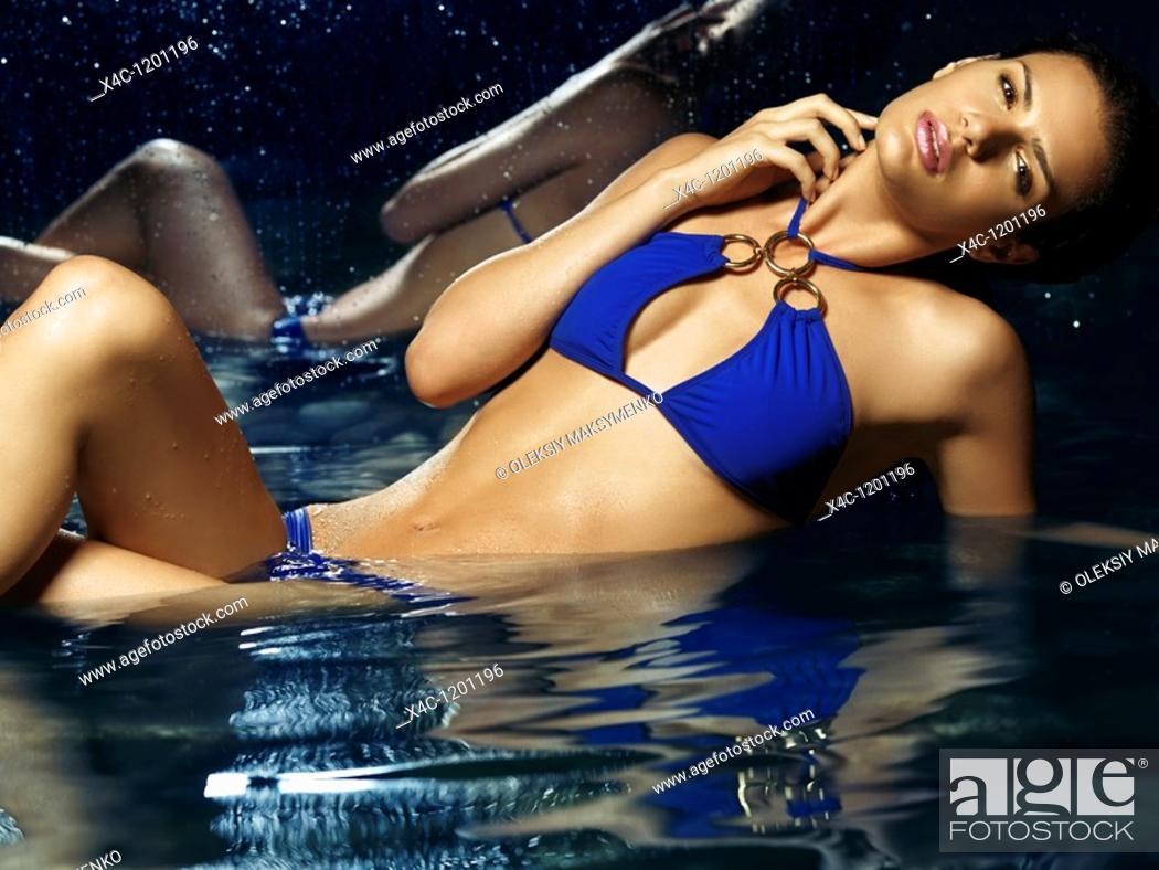 Stock Photo: Beautiful young woman in blue bikini in water  High fashion photo.