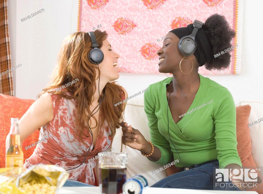 Stock Photo: Two women singing to headphones.