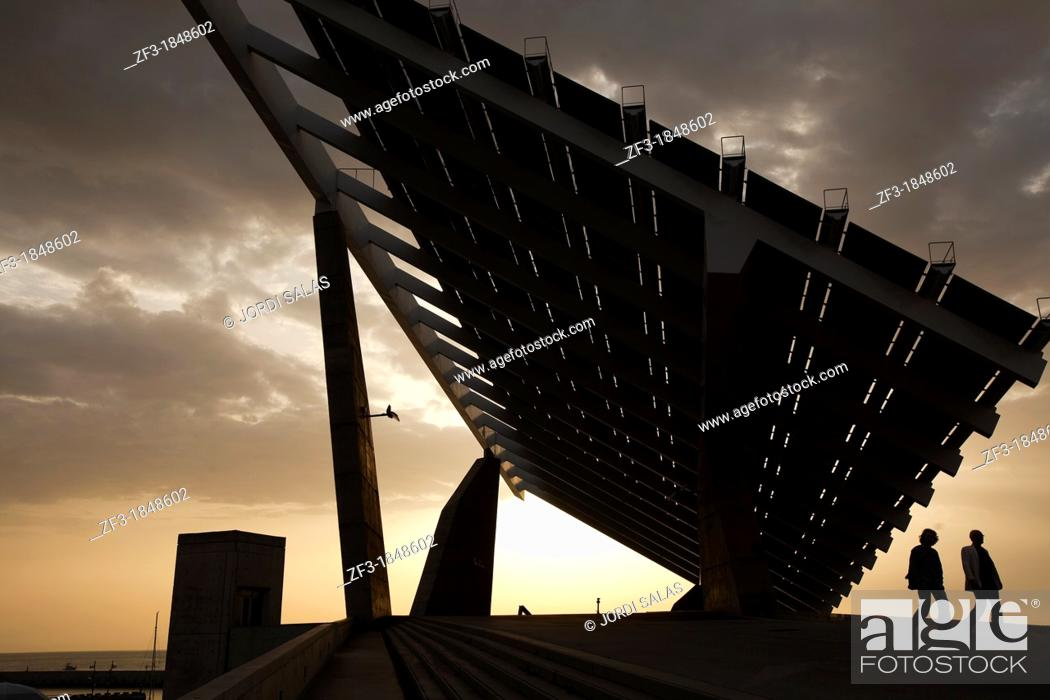 Stock Photo: Two people walking under a giant solar panel in Barcelona.