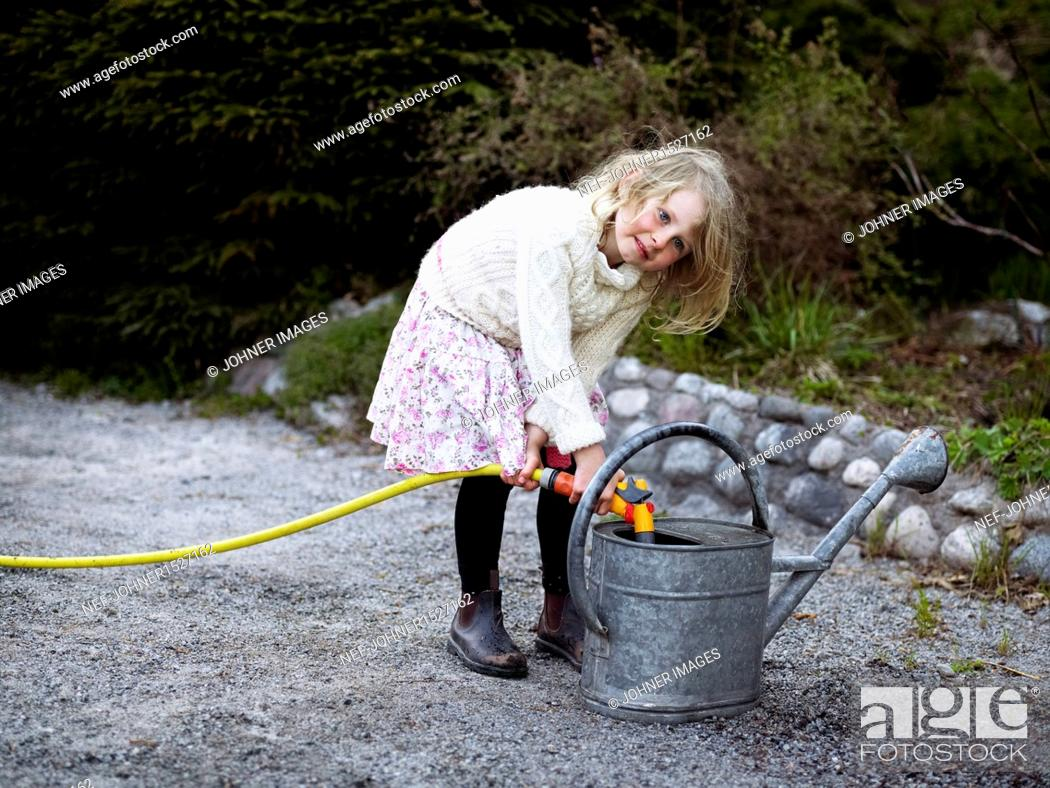 Stock Photo: Girl filling watering can.