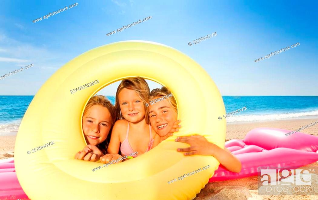 Stock Photo: Three happy girls friends on pink mattress looking through big rubber ring at the beach.