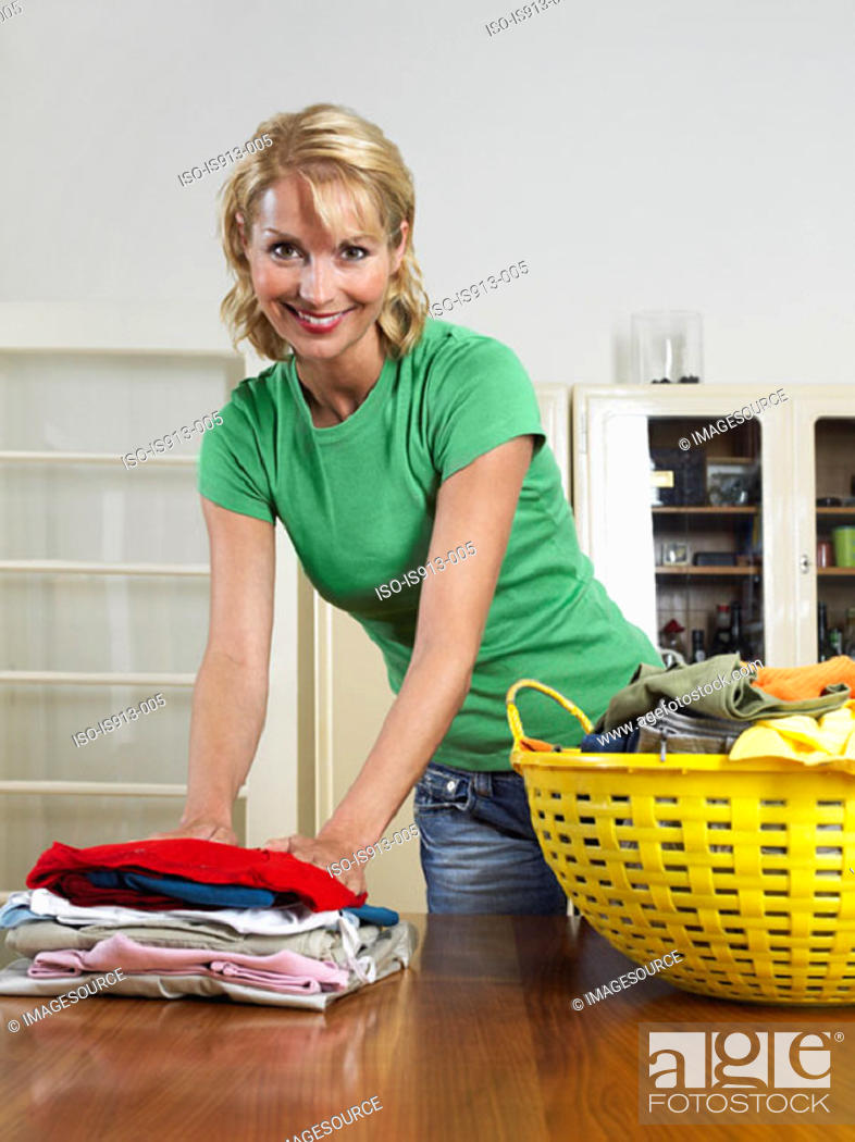 Stock Photo: Woman folding laundry.