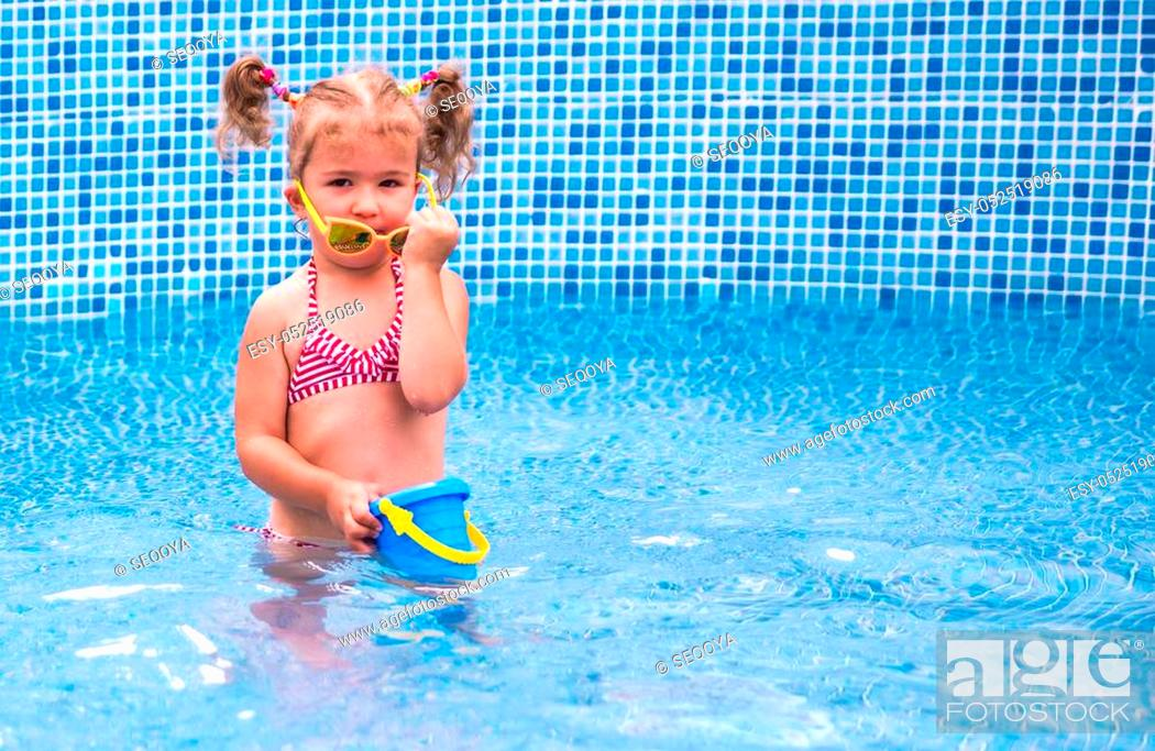 Stock Photo: Little beautiful girl resting in the pool and learning to swim.