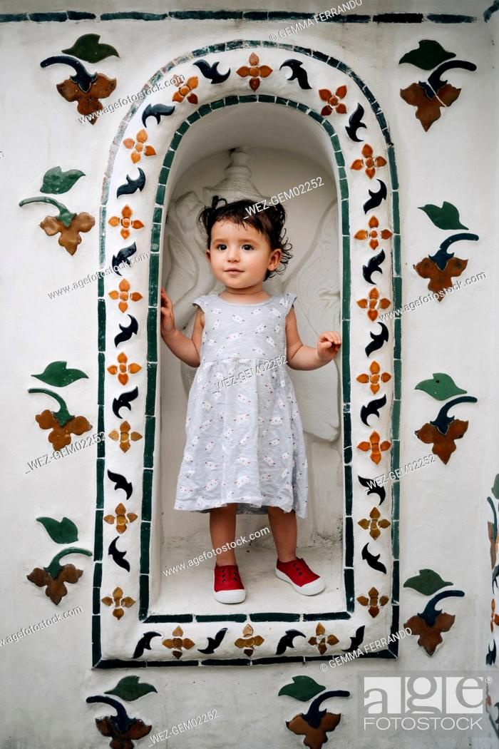 Imagen: Thailand, Bangkok, Wat Arun, cute baby girl standing in a niche of the temple.