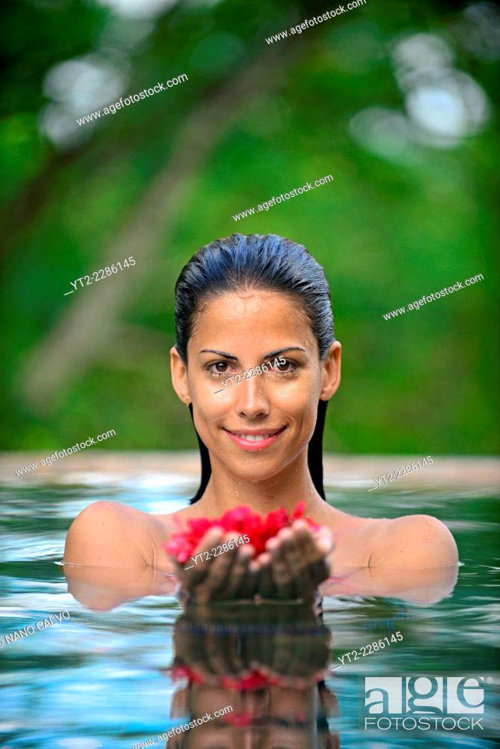 Stock Photo: Young attractive woman holding red flowers in an infinity edge swimming pool. The Dutch House, Galle, Sri Lanka.