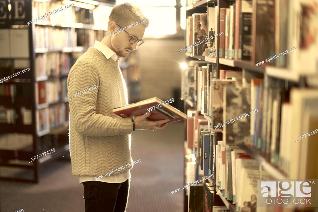 Imagen: man holding book, library, glasses, student, university.