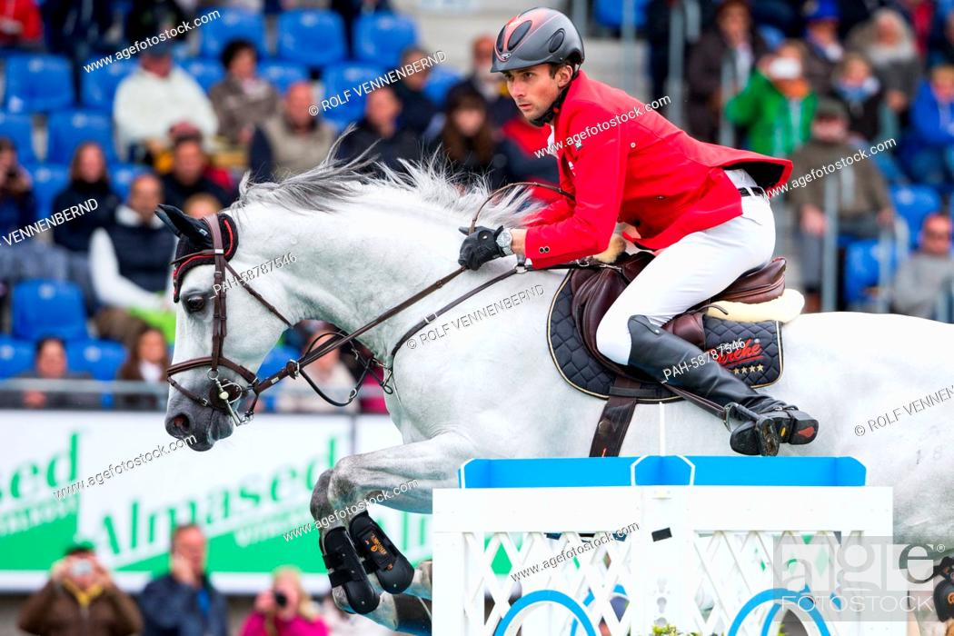 Stock Photo: German rider Denis Nielsen on his horse 'Cashmoaker' jumps a hurdle at the CHIO in Aachen,  Germany, 30 May 2015. He ranked third in the show jumping.