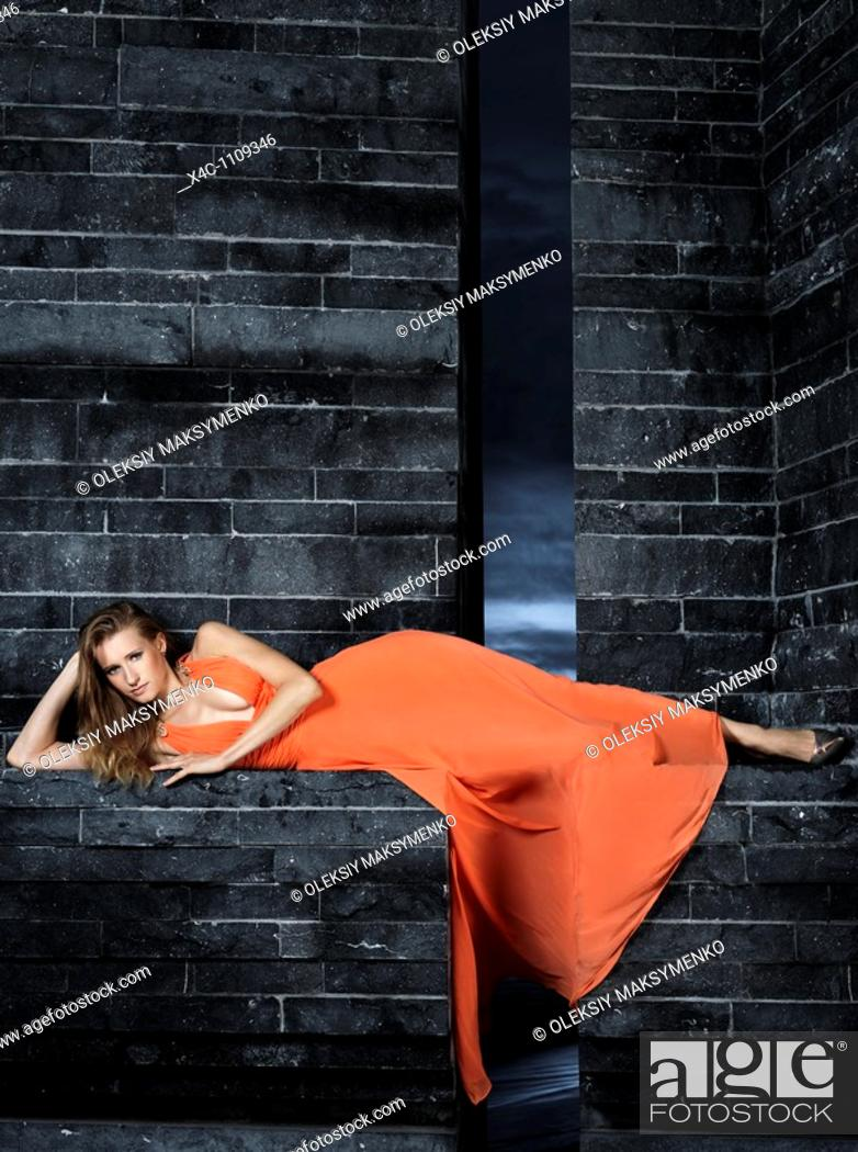 Stock Photo: Young woman in long orange dress posing on black granite wall.