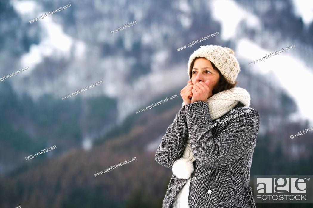 Stock Photo: Portrait of senior woman warming her hands in winter.