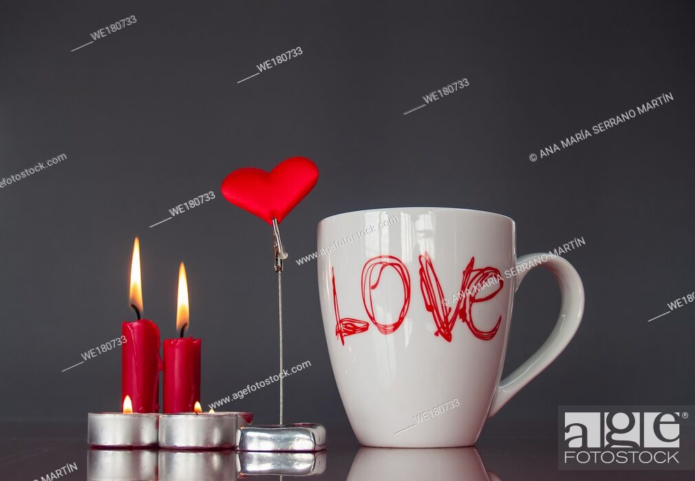Imagen: Concept of love Still life with red lit candles, a red heart and a breakfast cup with the word love.