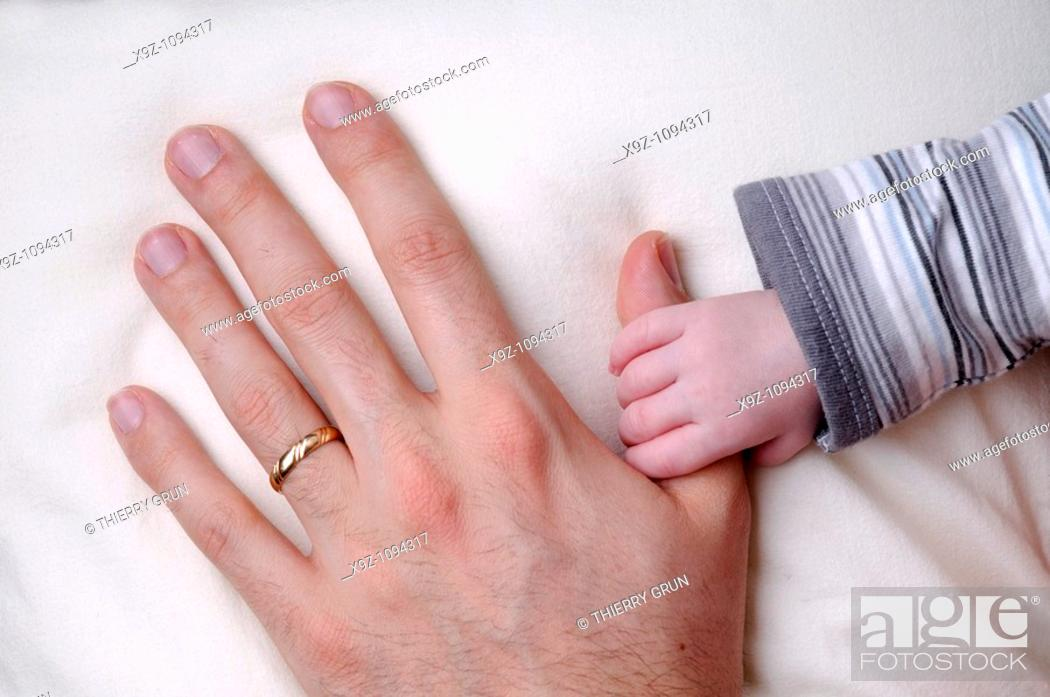 Stock Photo: Baby boy 3 weeks old holding father finger.