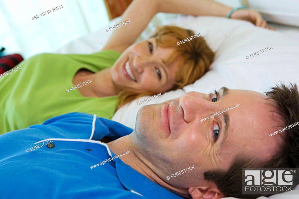 Stock Photo: Side profile of a young couple lying on the bed and smiling.
