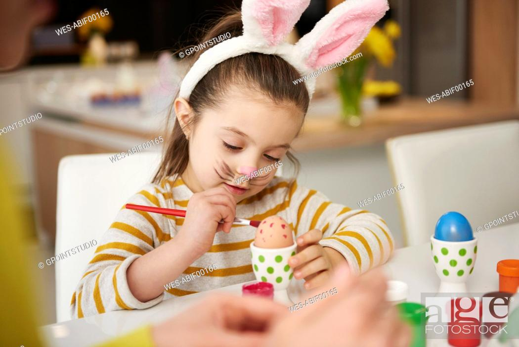 Stock Photo: Girl with bunny ears sitting at table painting Easter eggs.