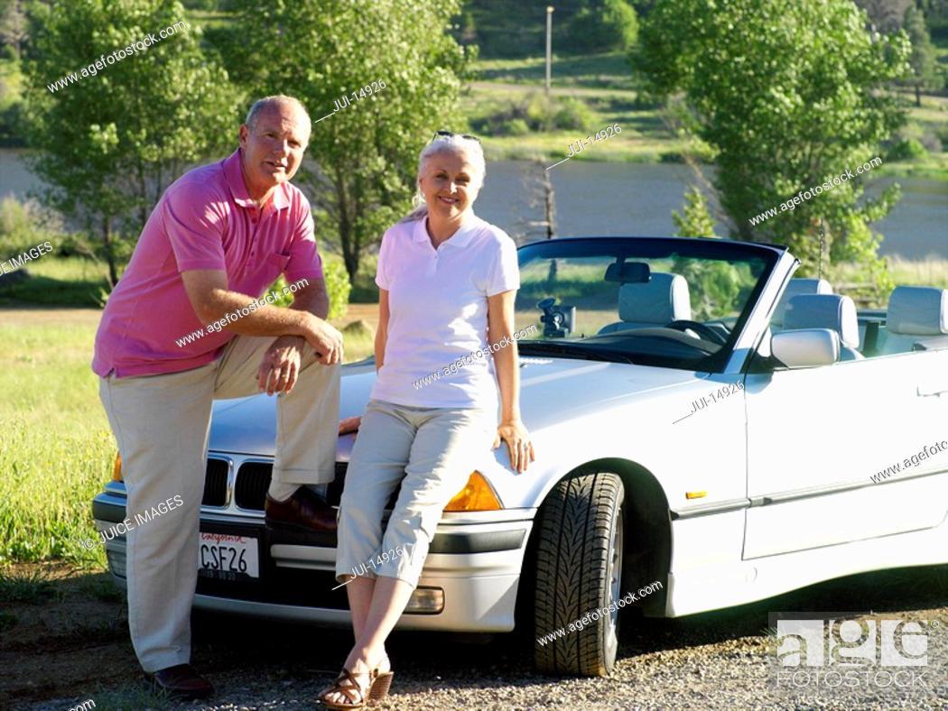 Stock Photo: Couple on bonnet of convertible car, portrait.
