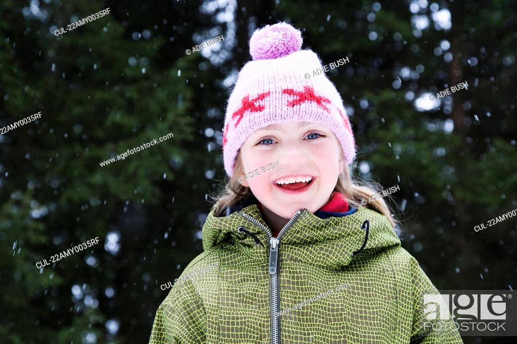 Stock Photo: Young girl in wooly hat with snow flakes.