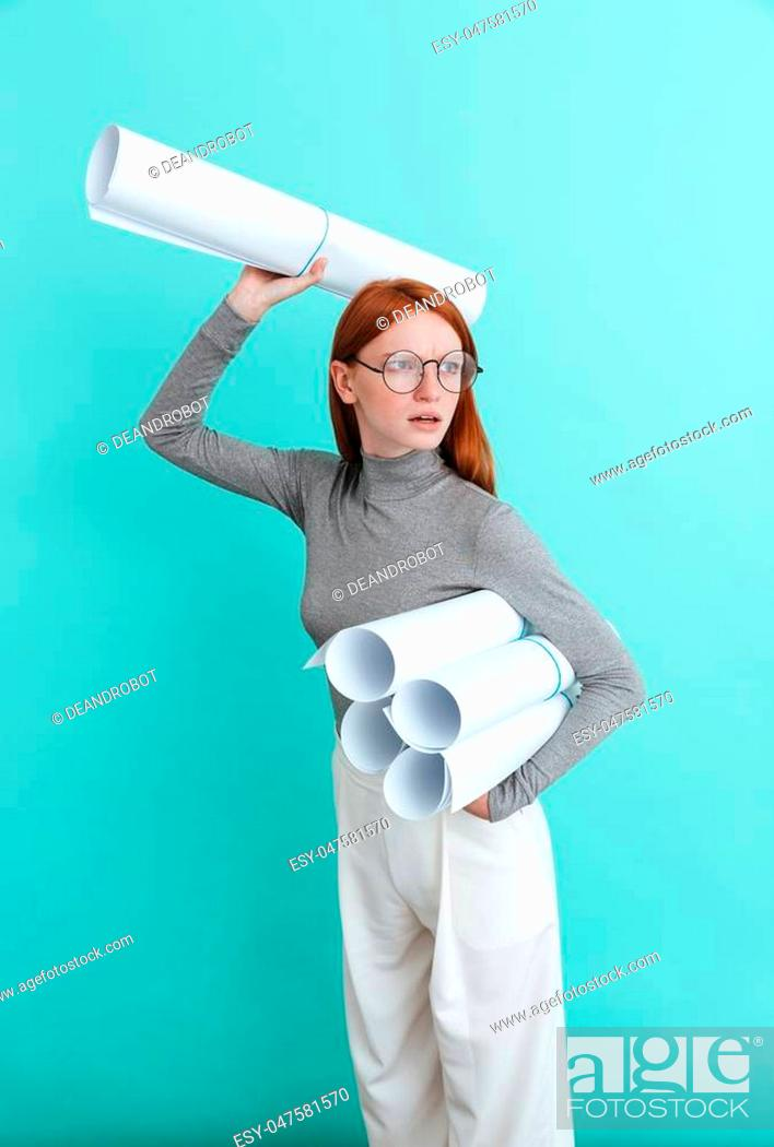 Stock Photo: Serious redhead young woman holding and throwing blueprints over blue background.