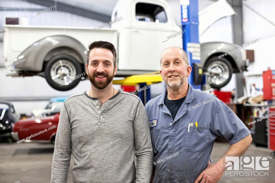 Stock Photo: A portrait of a Caucasian senior car mechanic and his son in their classic car repair shop.