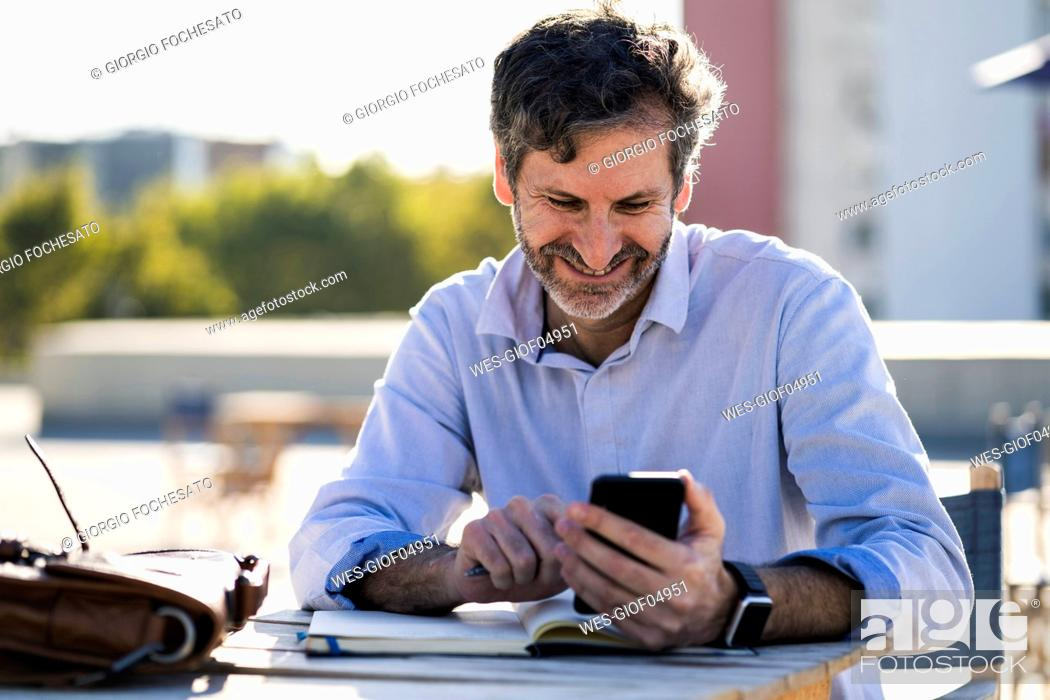 Stock Photo: Smiling mature man sitting at outdoor table with cell phone and notebook.