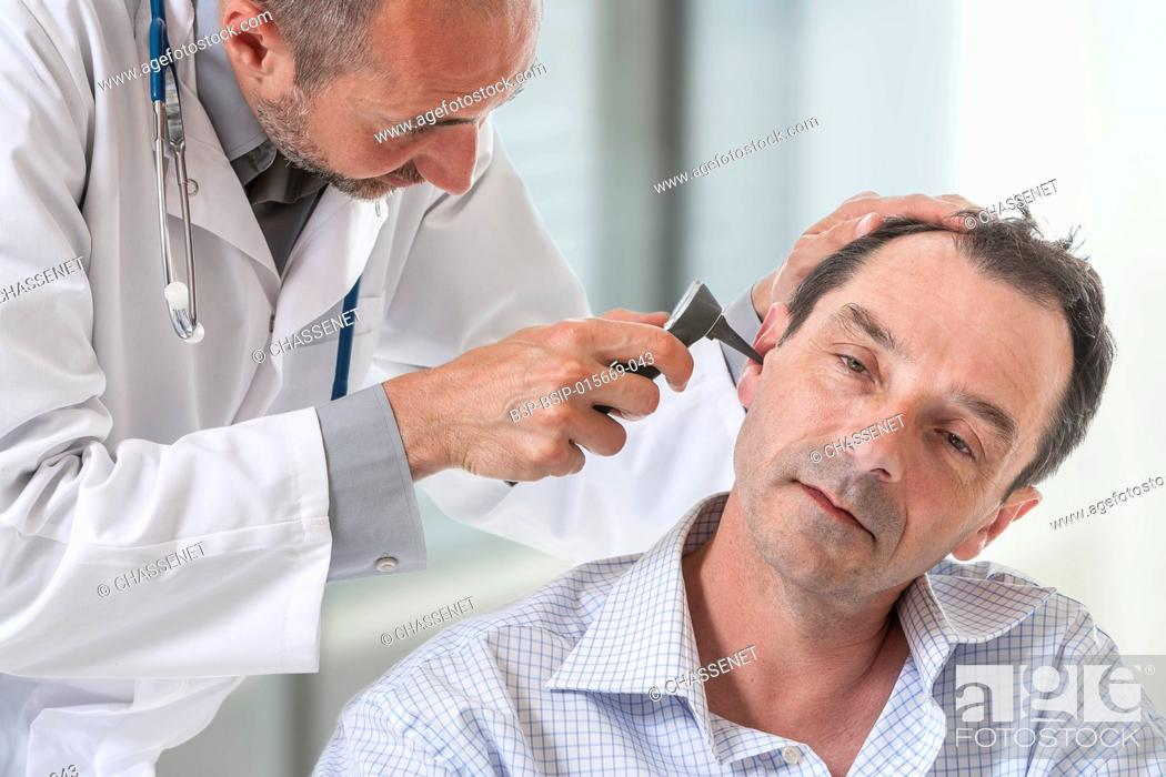Stock Photo: Doctor examining a patient's ear.