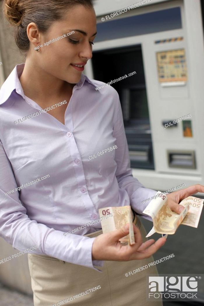 Stock Photo: Business woman withdrawing cash.