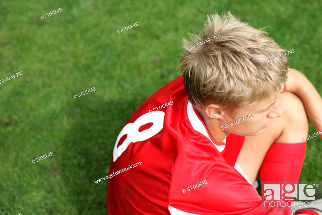 Stock Photo: Soccer player sitting on grass.