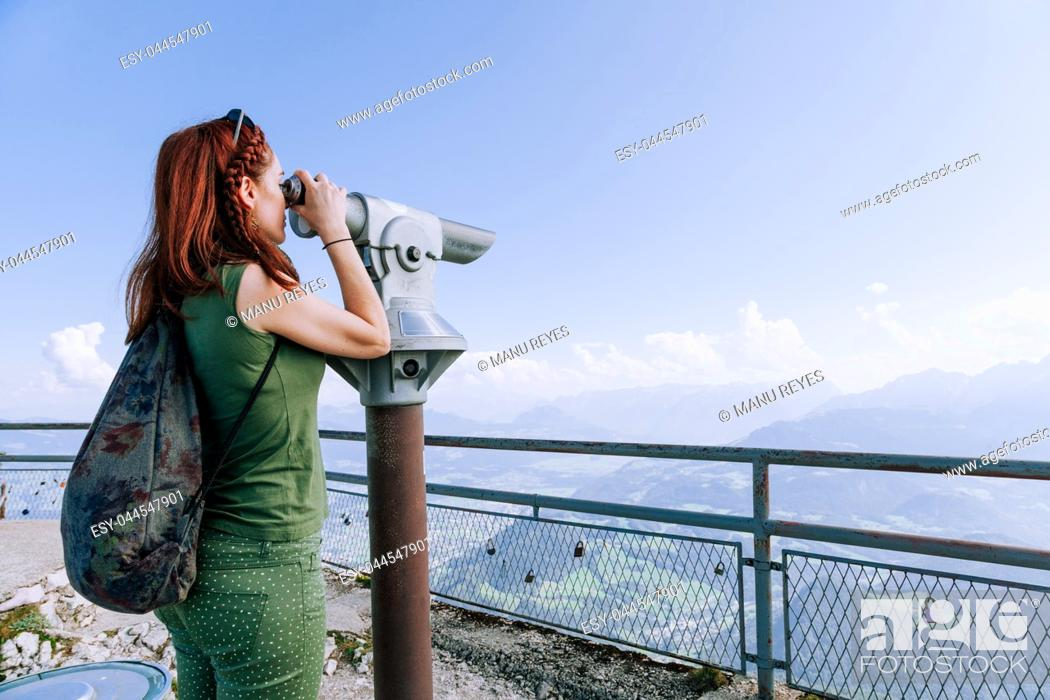Imagen: Young redhead woman viewing the mountains and sunset in Coin Operated Binocular viewer traveler. Untersberg, Salzburgo, Austria.