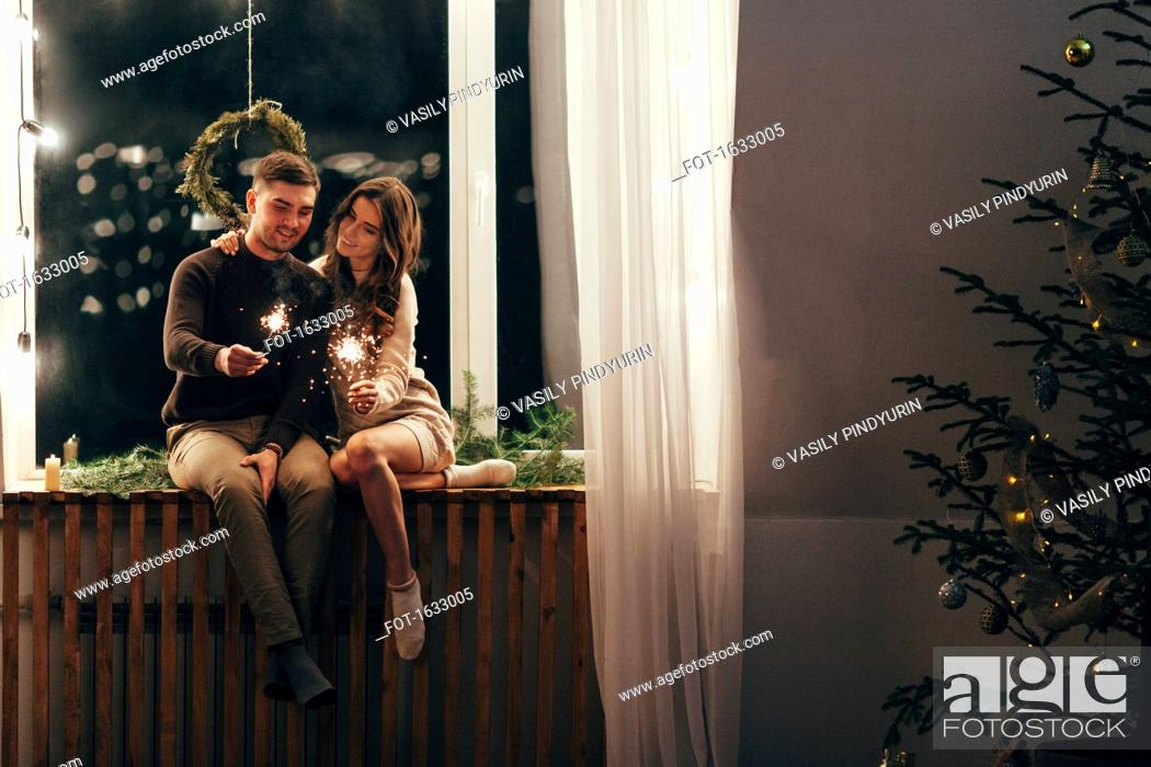Stock Photo: Happy couple playing with sparklers while sitting on window sill during Christmas.
