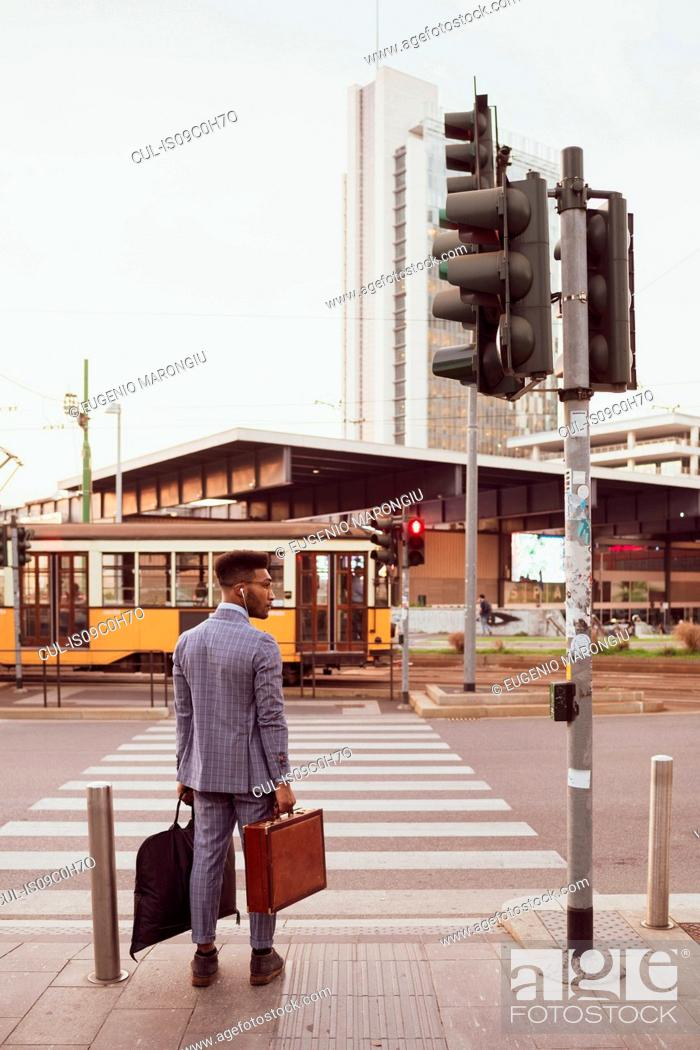 Imagen: Businessman waiting by pedestrian crossing, Milano, Lombardia, Italy.
