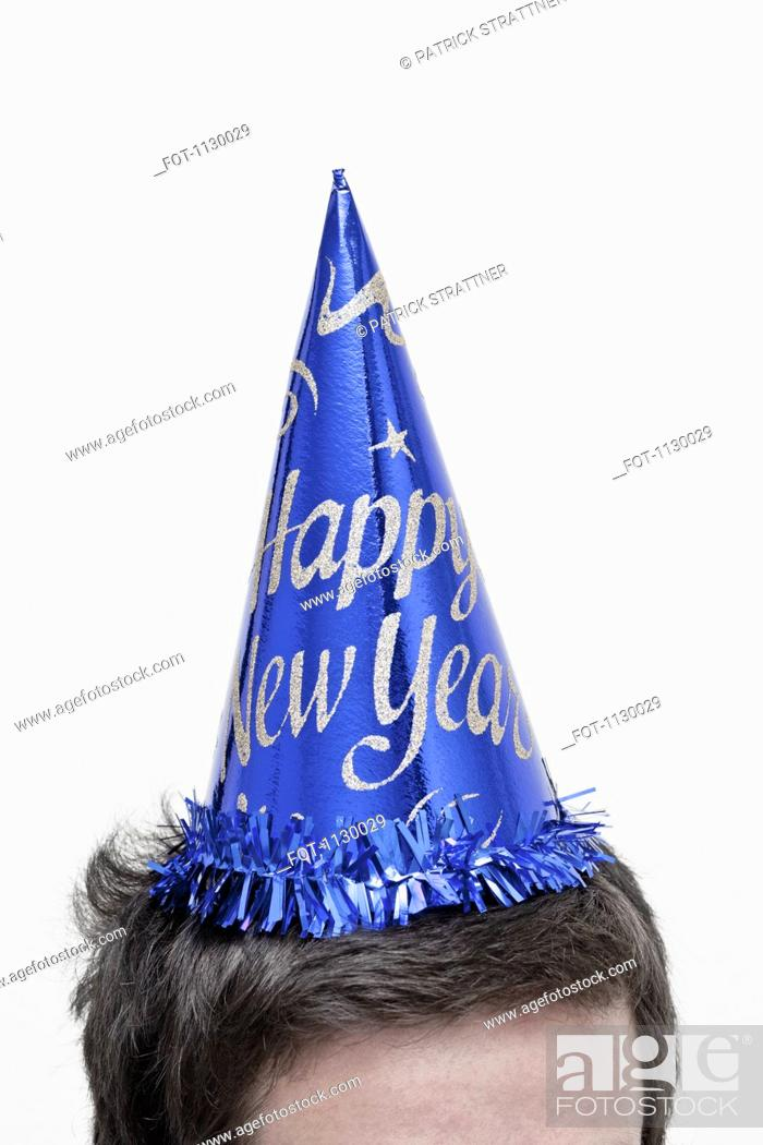 Stock Photo: A man wearing a New Year's Eve party hat, top of head.