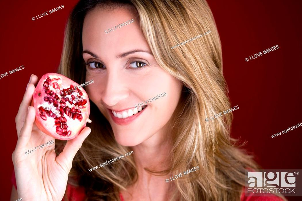 Stock Photo: A mid adult woman holding half a pomegranate.