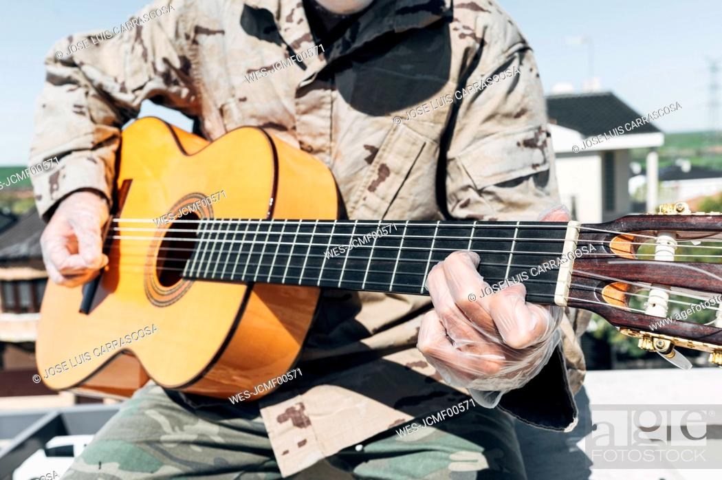 Imagen: Soldier playing the guitar, with protective gloves.