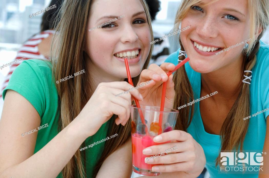 Imagen: Portrait of two young women drinking juice in a restaurant.