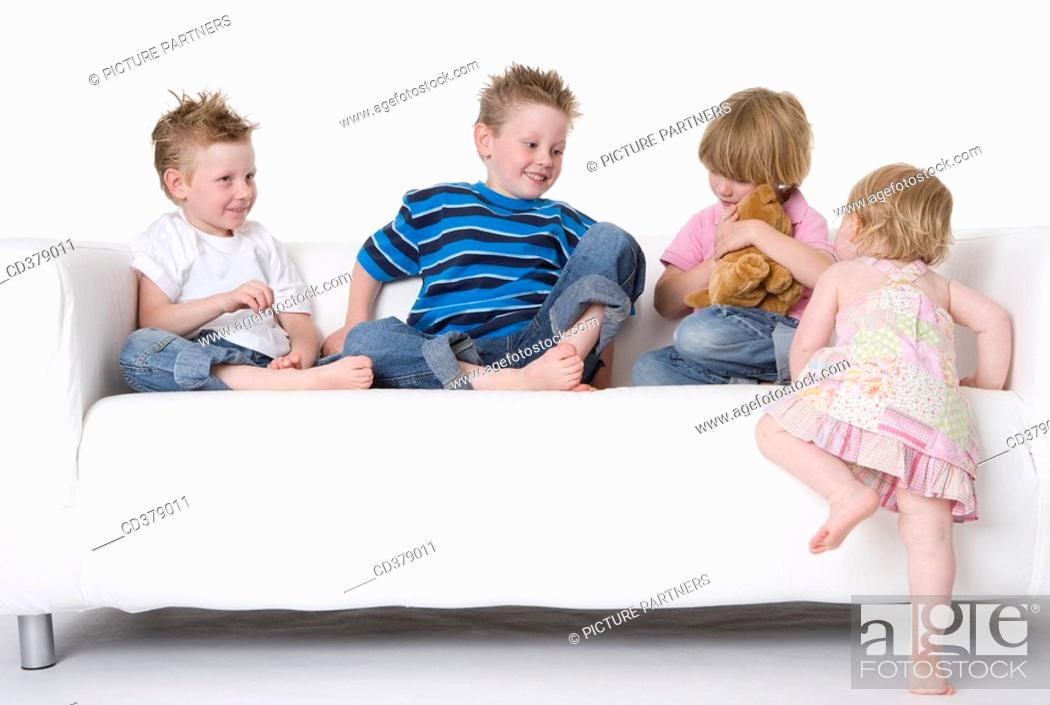 Stock Photo: Three boys and a girl sitting on a bench.