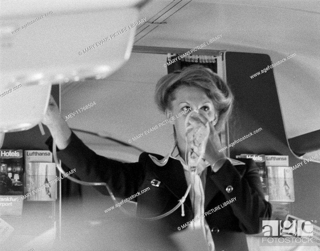 Air stewardess demonstrating oxygen mask on board a passenger plane