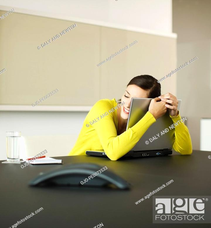 Stock Photo: Smiling businesswoman hugging laptop in conference room.