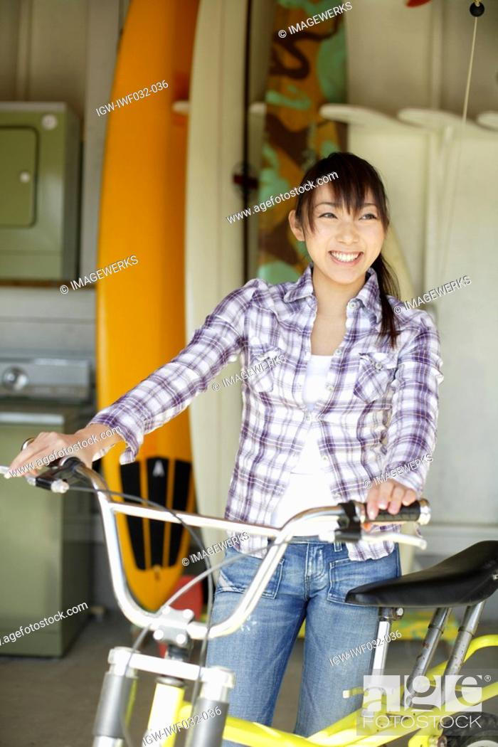 Stock Photo: View of a smiling woman with bicycle.