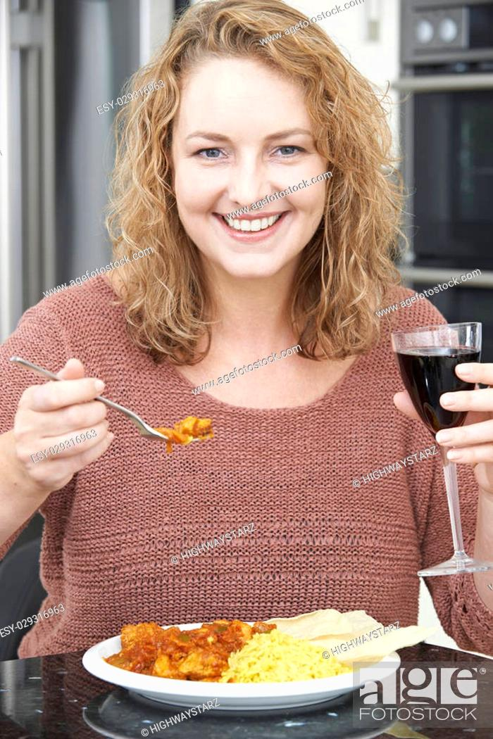 Stock Photo: Woman Eating Takeaway Curry And Drinking Wine.