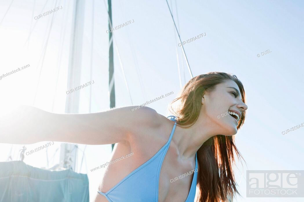 Stock Photo: Young brunette woman on yacht, laughing.