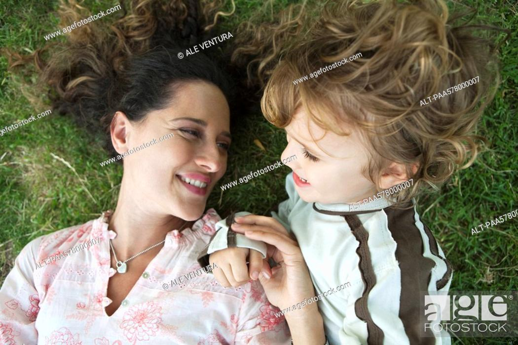 Stock Photo: Mother and young son lying on the ground together.