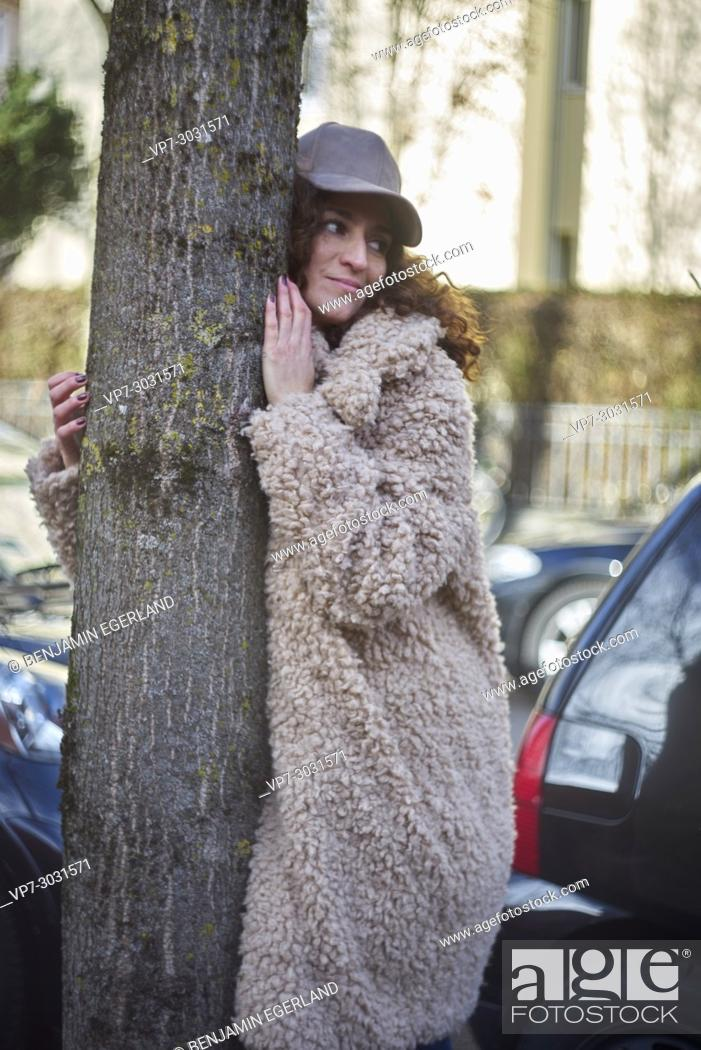 Imagen: multi-cultural woman embracing tree while standing in a city street full of cars. Wearing Coat and cap. Fashion blogger Aslihan Kiratli.