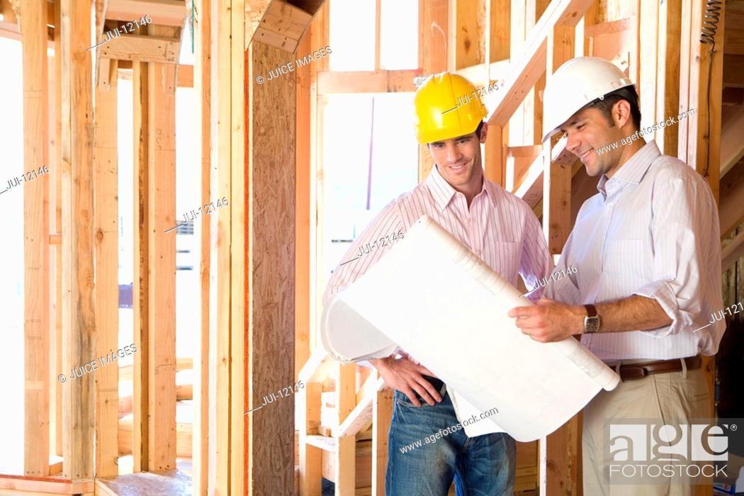 Stock Photo: Architect showing blueprint to man in partially built house.