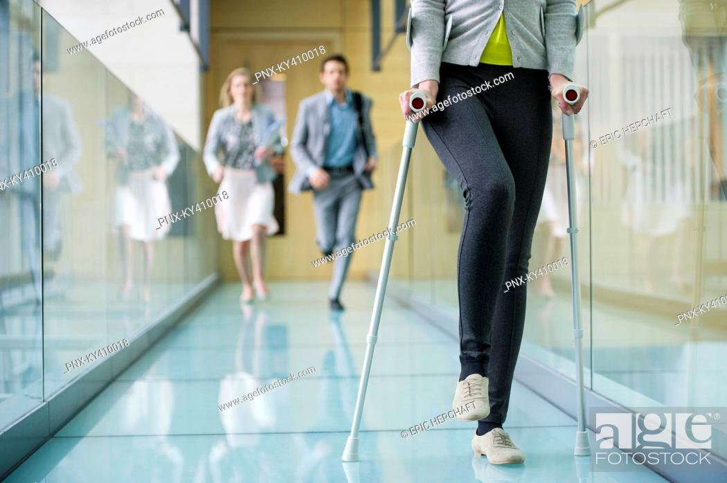 Stock Photo: Disabled woman walking with a man and a woman running behind her.
