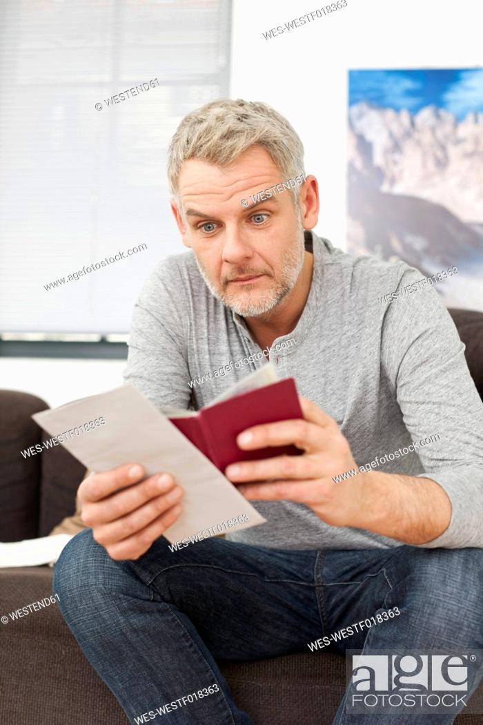 Stock Photo: Germany, Leipzig, Mature man looking document.