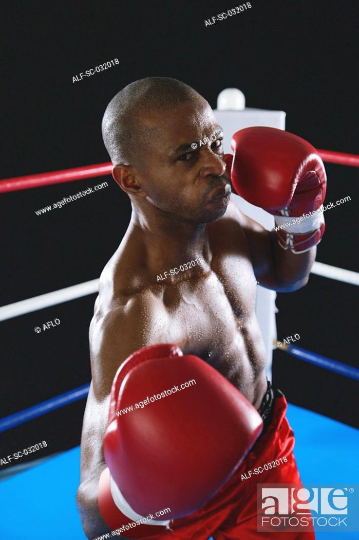 Stock Photo: African boxer wearing red Boxing gloves ready to punch.