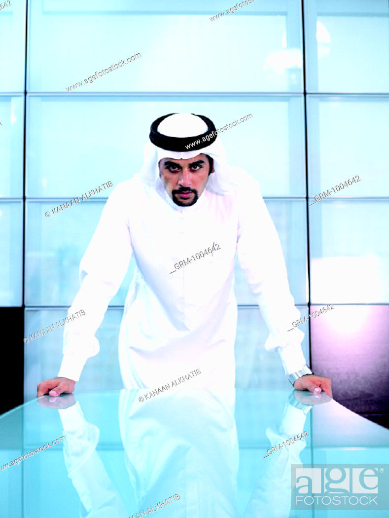 Stock Photo: Arab businessman standing at conference table.