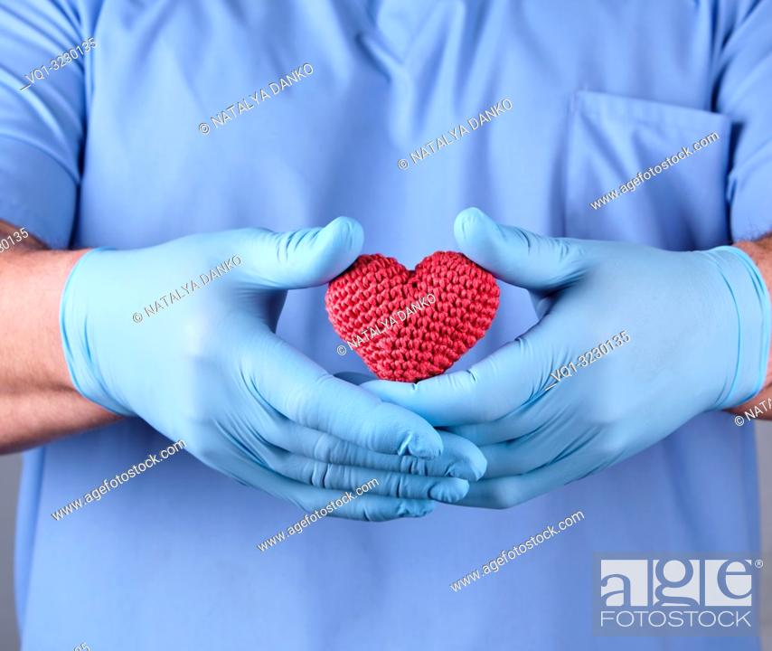 Imagen: doctor with blue latex gloves holding a red heart, selective focus.