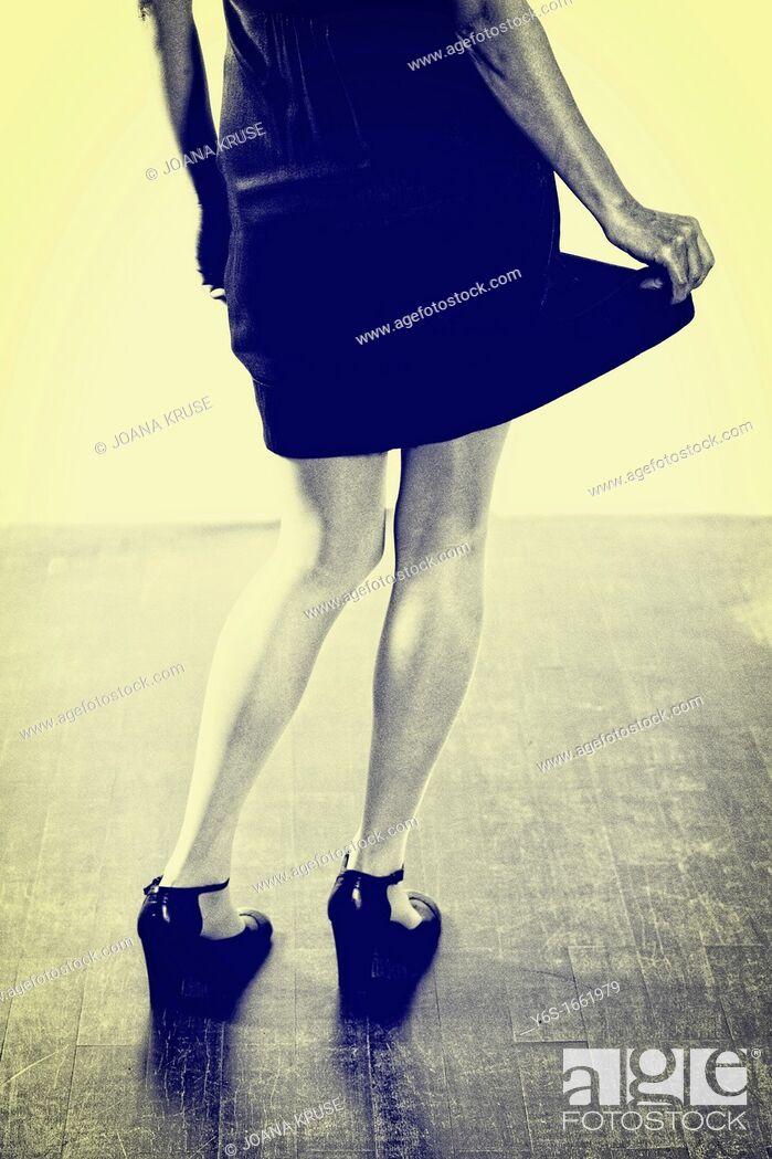 Stock Photo: Woman in black dress swings her skirt.